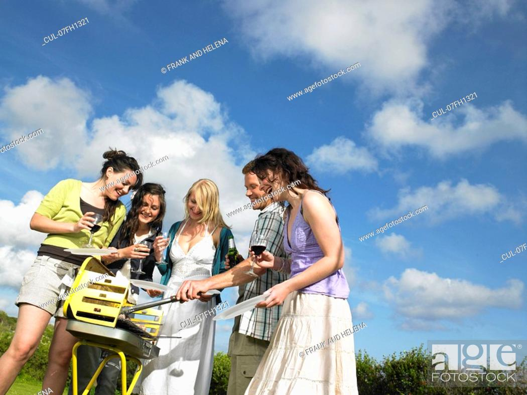 Stock Photo: Group of young people around barbecue.