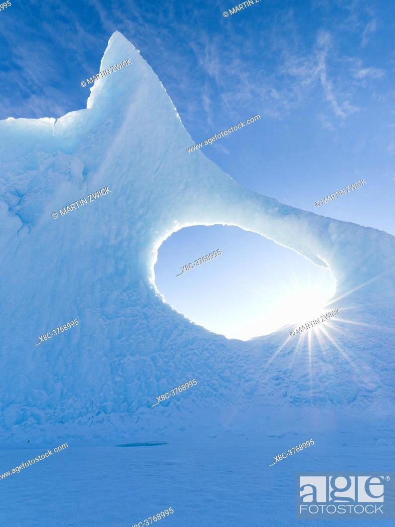 Stock Photo: Iceberg frozen into the sea ice of the Uummannaq fjord system during winter in the the north west of Greenland, far beyond the polar circle.