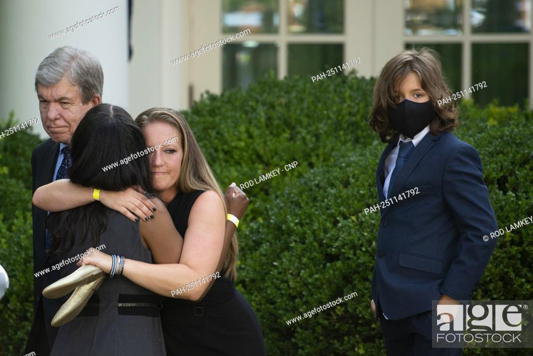 """Stock Photo: Anne Winters, left, sister of USCP Officer Howard Liebengood gets a hug from Shannon Terranova, right, ex-wife of USCP Officer William """"""""Billy"""""""" Evans."""