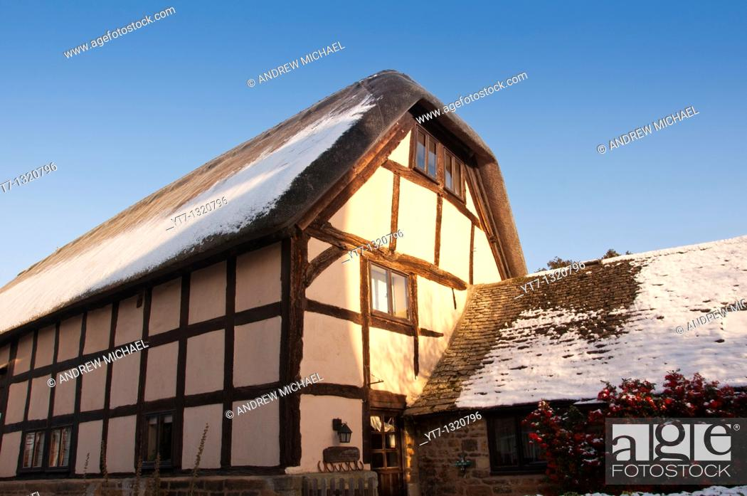 Stock Photo: A thatched barn conversion in the Cotswold village of Stanton, Gloucestershire, England.