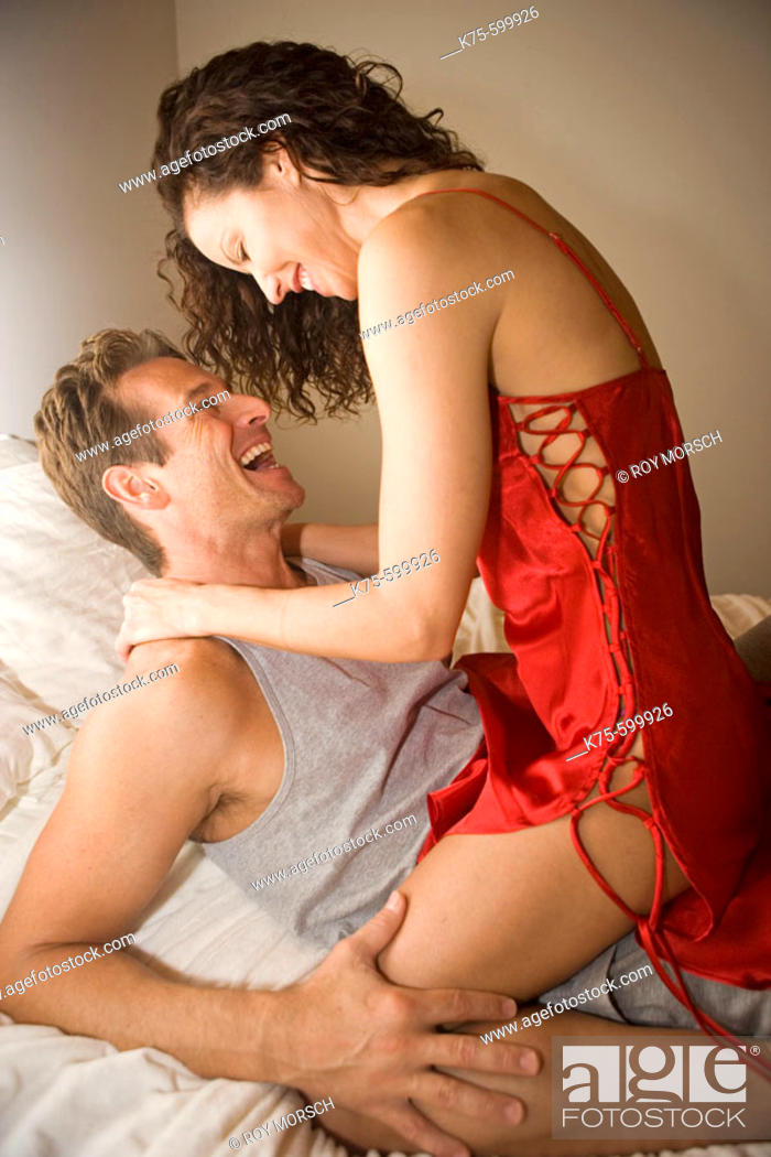Stock Photo: Caucasian couple, age 30's to 40's, bed, playful, lingerie.