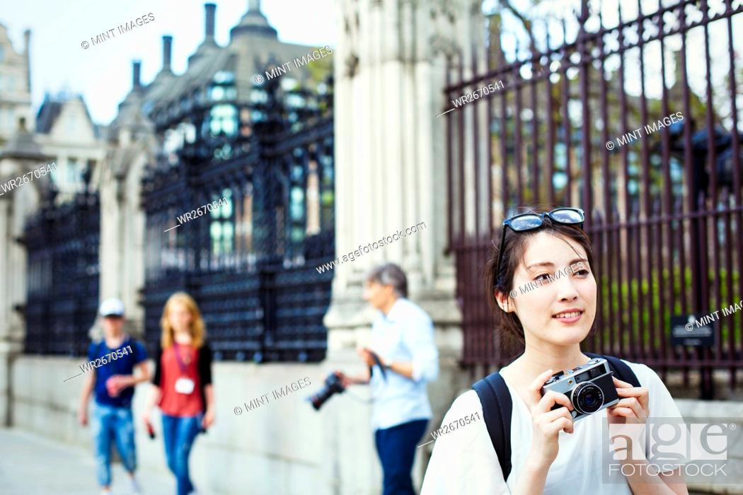 Imagen: Young Japanese woman enjoying a day out in London, holing a camera.