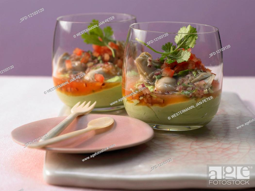 Stock Photo: Marinated oysters on avocado cream with diced tomatoes.