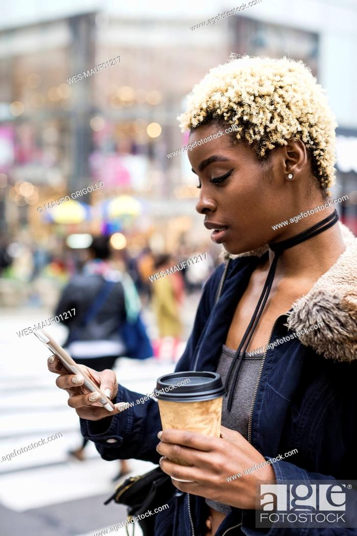Imagen: USA, New York City, portrait of young woman with coffee to go.