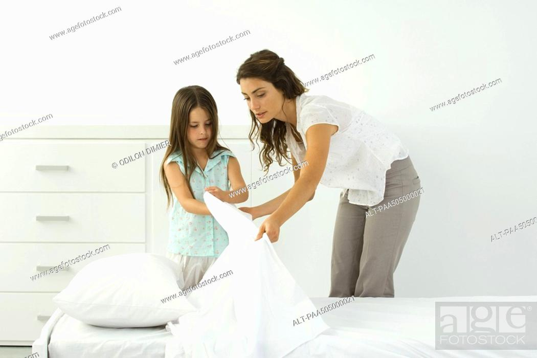 Stock Photo: Mother and daughter making bed together.