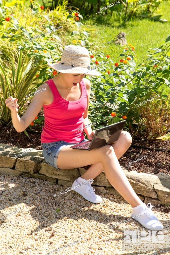 Imagen: Angry young woman using laptop in garden.