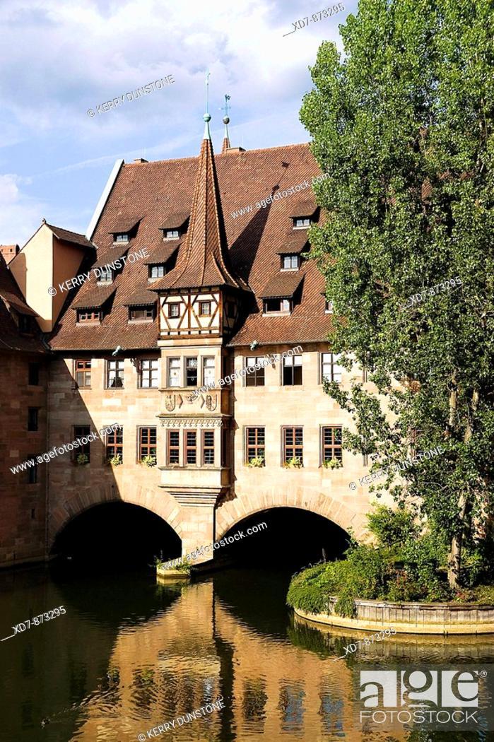 Stock Photo: Germany Bavaria Nuremberg Heilig-Geist-Spital Old people's residences above the River Pegnitz.
