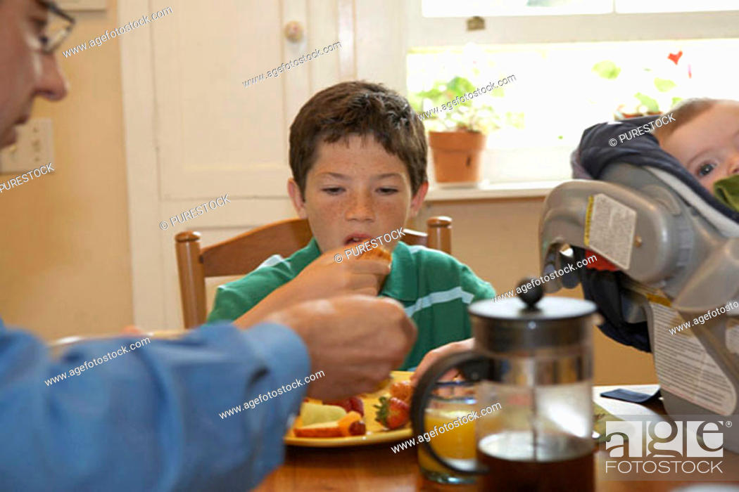 Stock Photo: Boy having breakfast with his father.