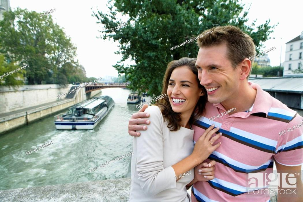 Stock Photo: Young couple by river Seine with tourist boat in background, Paris, France.