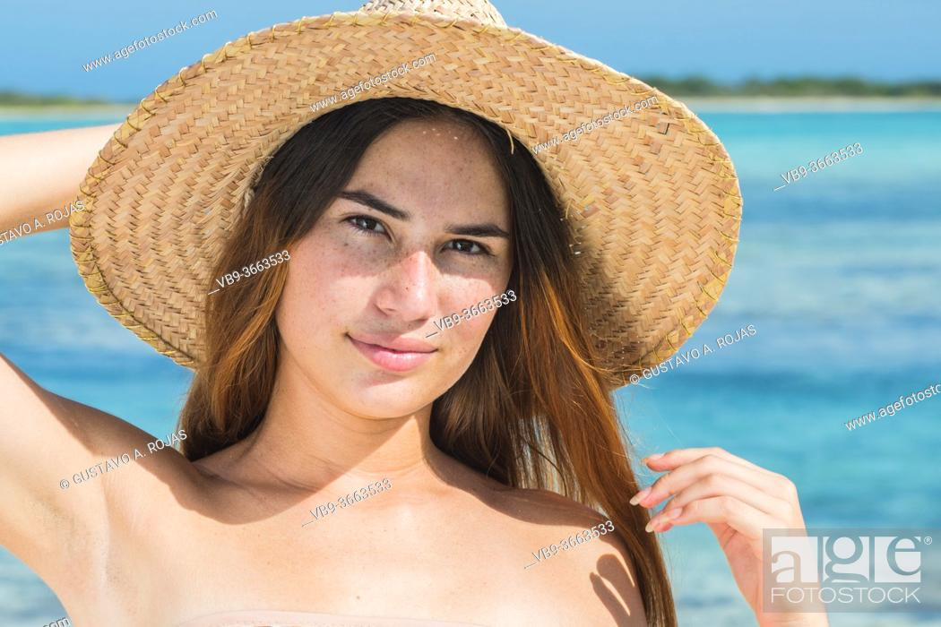 Photo de stock: Beautiful caucasian woman with straw hat on tropical beach. Portrait of happy young woman smiling at camera.