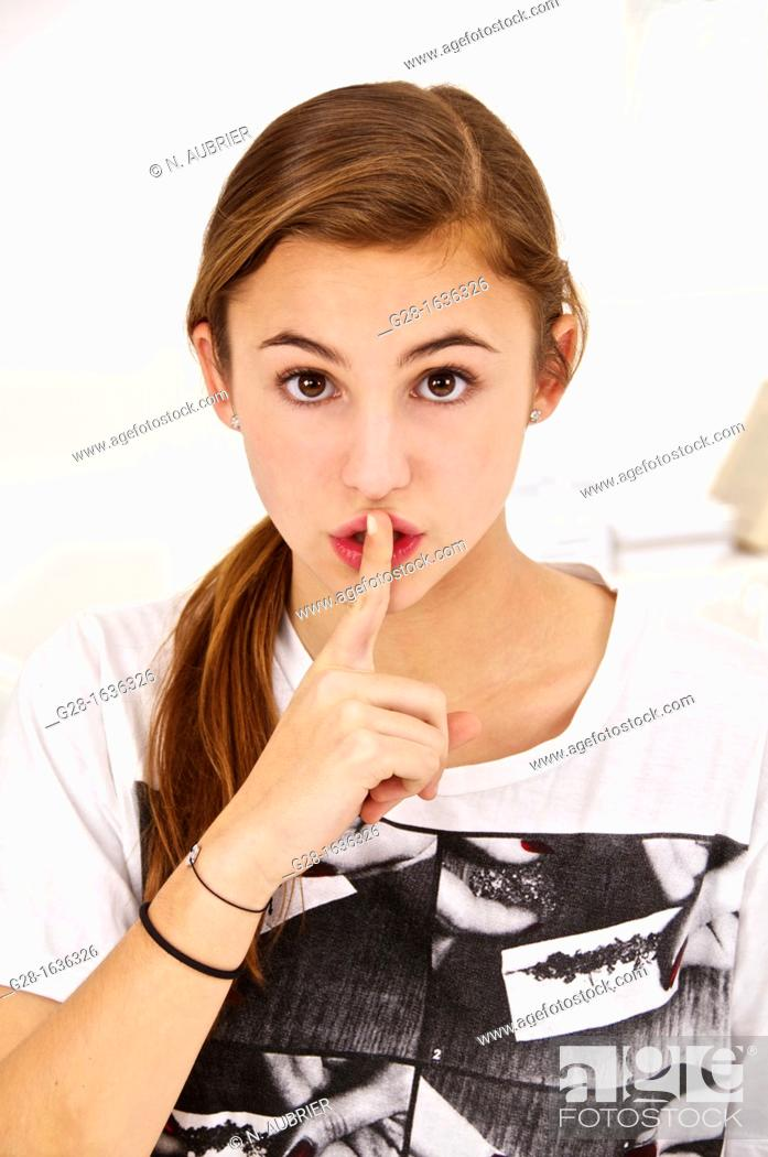 Stock Photo: Young teenage girl putting her finger in front of her mouth.