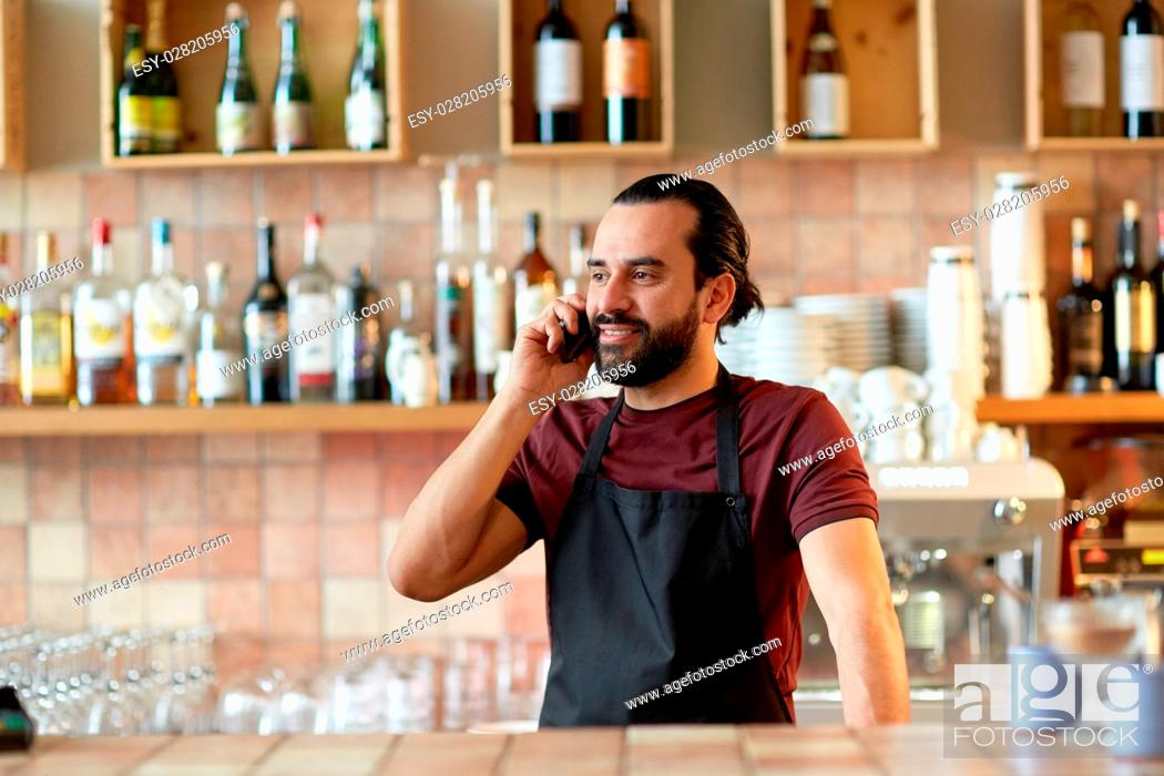 Stock Photo: small business, communication, people and service concept - happy man or waiter in apron calling on smartphone at bar or coffee shop.