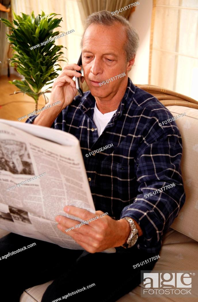 Stock Photo: Mature man reading newspaper and talking on cell phone.