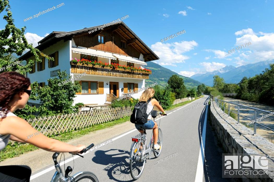 Stock Photo: Cyclists leave the mediaeval walled town of Glurns in the Alto Adige region of Italy  Riverside chalet on the Via Lungo Adige.