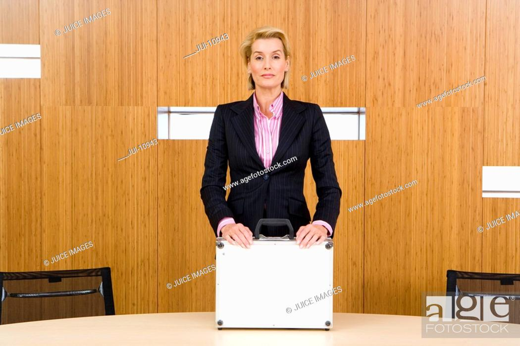 Stock Photo: Businesswoman standing at conference table with hands on briefcase, portrait.