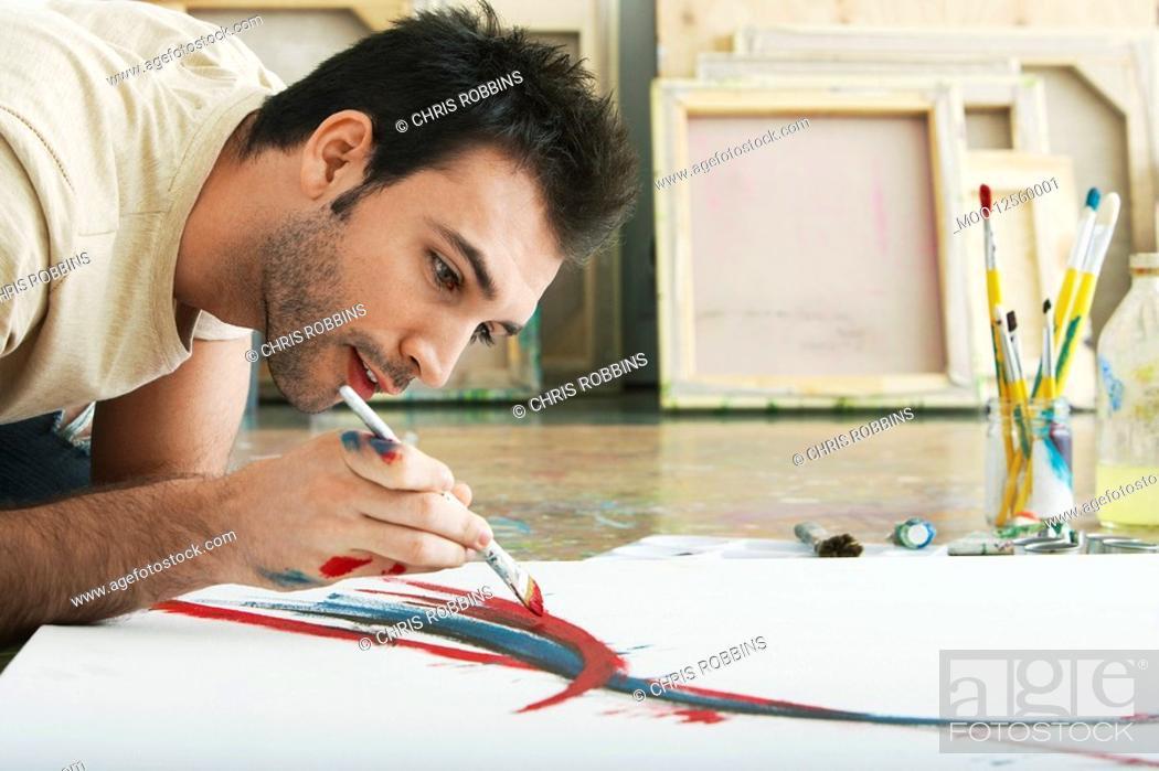 Stock Photo: Man painting on canvas on studio floor.