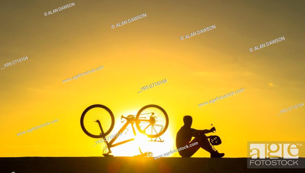 Stock Photo: A mountain biker watches the sun rise over the Atlantic ocean from sea wall. Avenida Maritima, Las Palmas, Gran Canaria, Canary Islands, Spain. Europe.