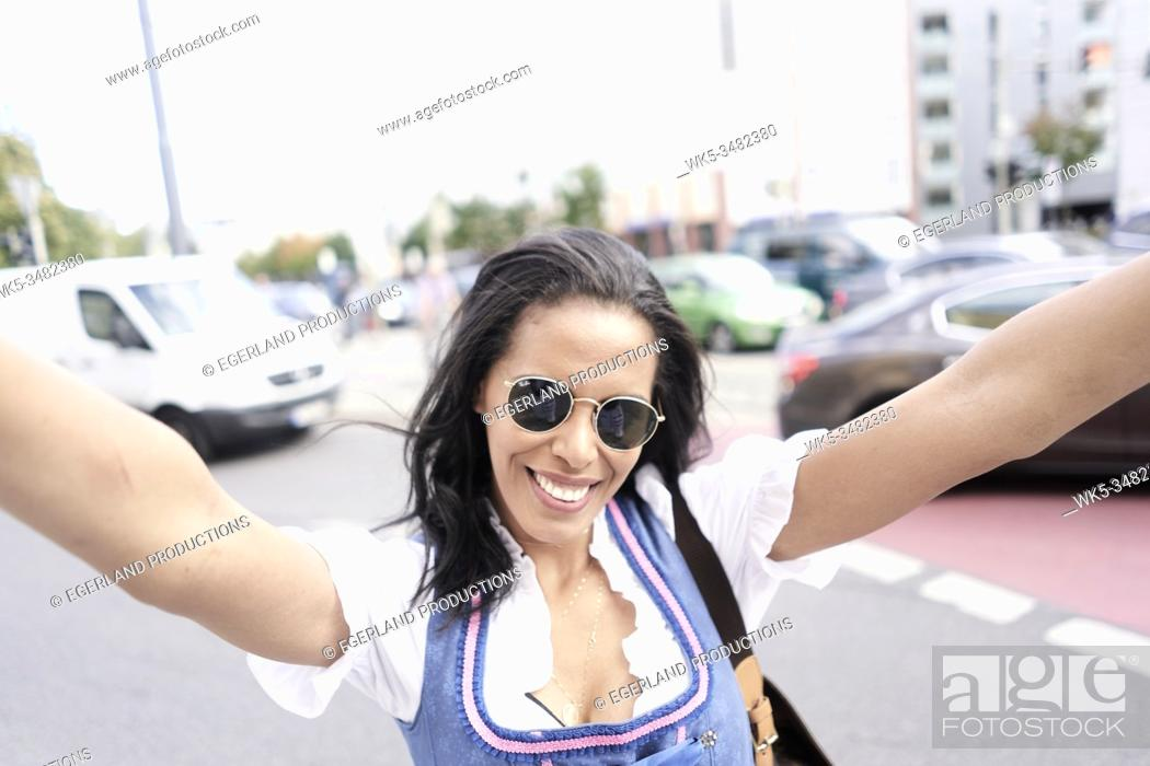 Stock Photo: lighthearted Brazilian woman wearing Bavarian Dirndl, feeling free easy. Munich, Germany.