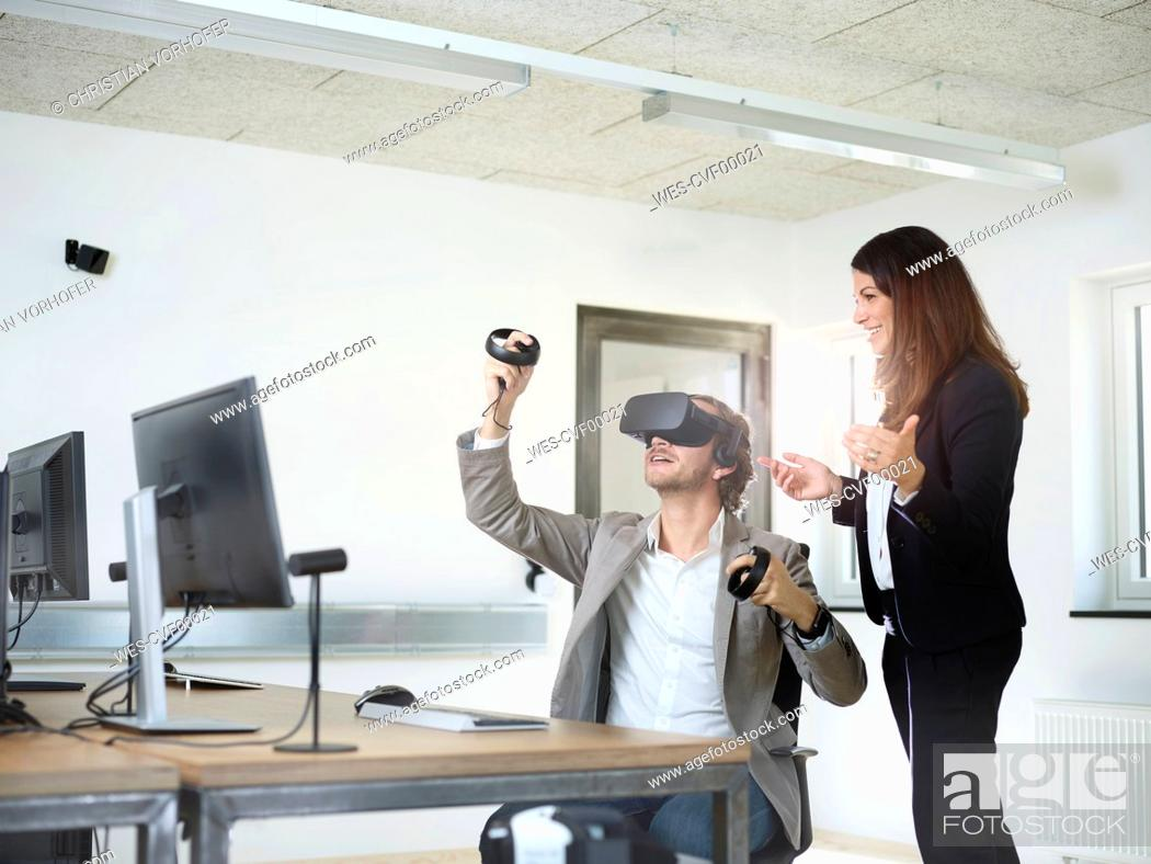 Stock Photo: Woman with man wearing VR glasses in office.