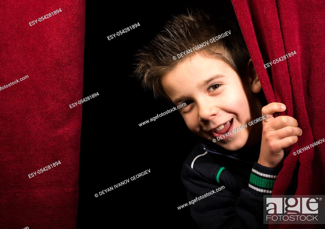 Stock Photo: Child appearing beneath the curtain. Red curtain.