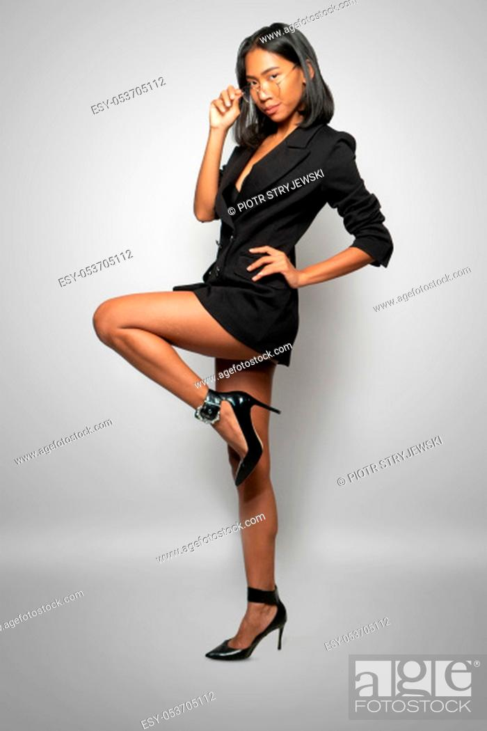 Stock Photo: Portrait of attractive young Asian woman in elegant black blazer, high heels and glasses posing over light gray wall background.
