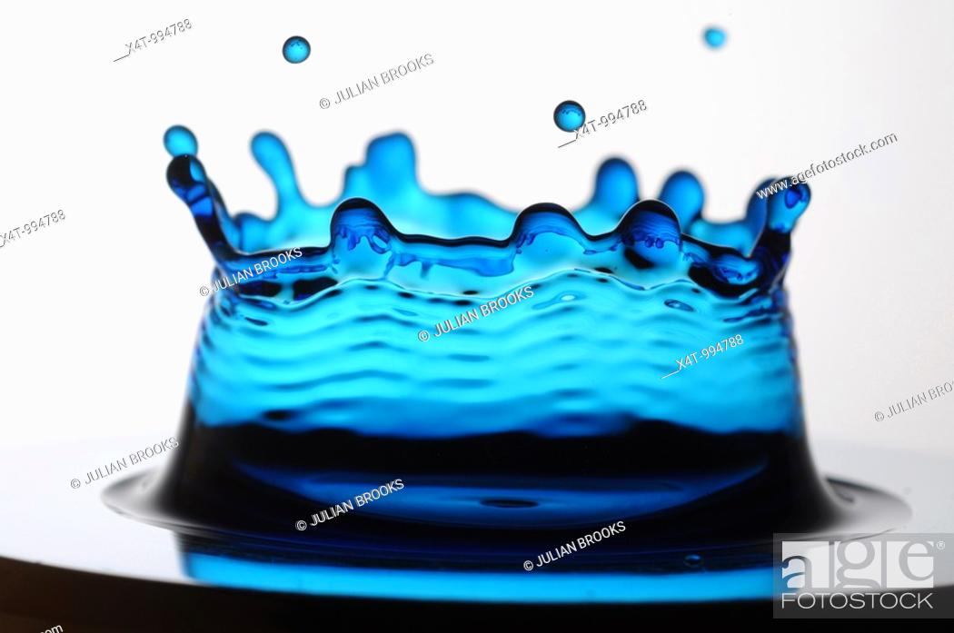 Stock Photo: A single drop of blue liquid forming a coronet as it lands.