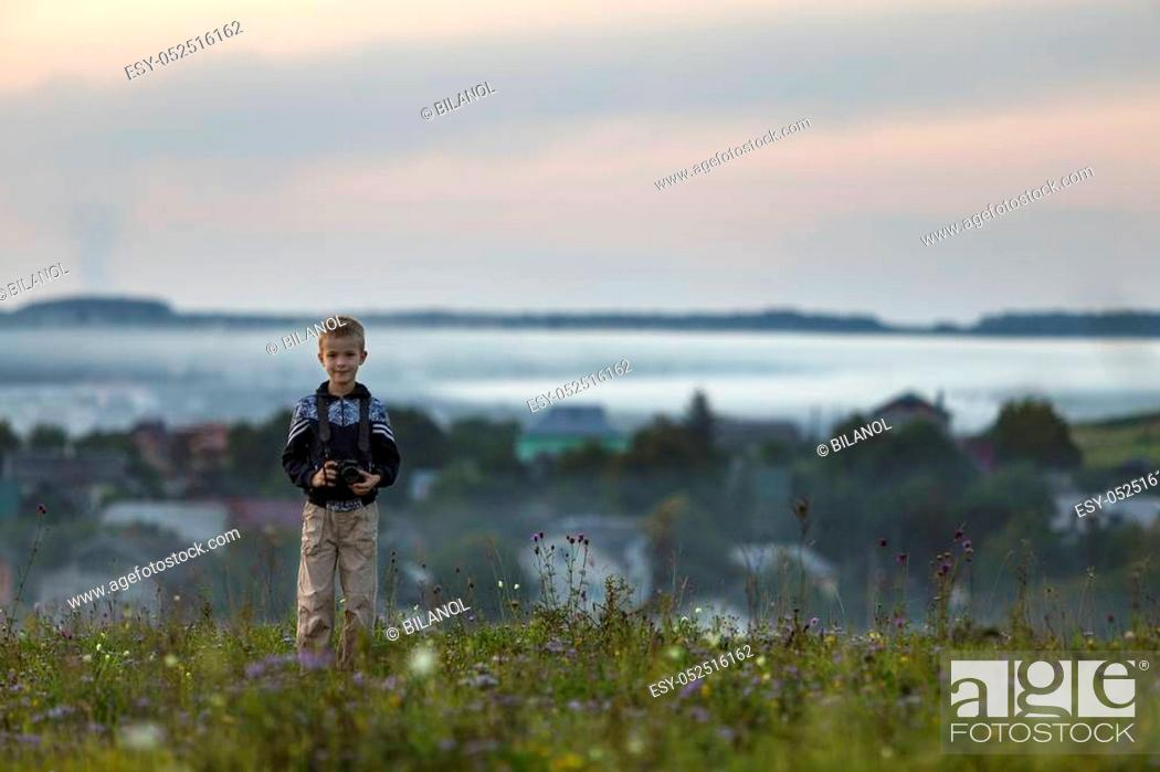 Stock Photo: Young blond cute smiling happy child boy with photo camera standing on grassy hill top on spring or summer day on foggy blurred blue view of village houses.