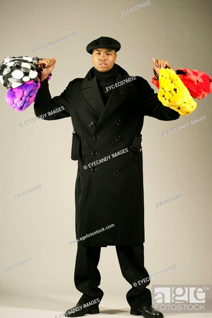 Stock Photo: Young African American man holding stylish purses.