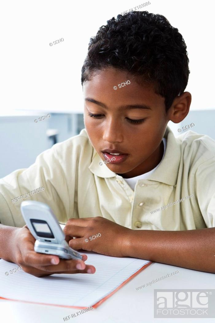 Stock Photo: School boys 10-13 using mobile phone in classroom, sitting looking at phone.