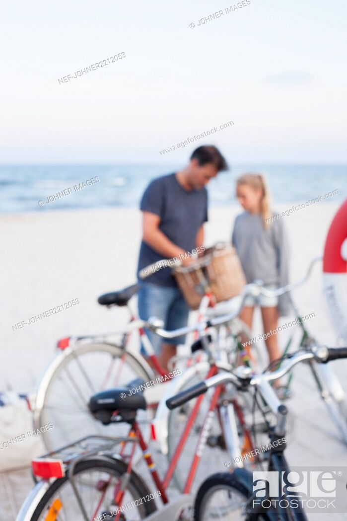 Imagen: Bicycles on beach, father with daughter on background.