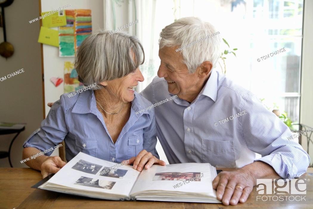 Stock Photo: Germany, Bavaria, Senior couple with photo album, smiling.