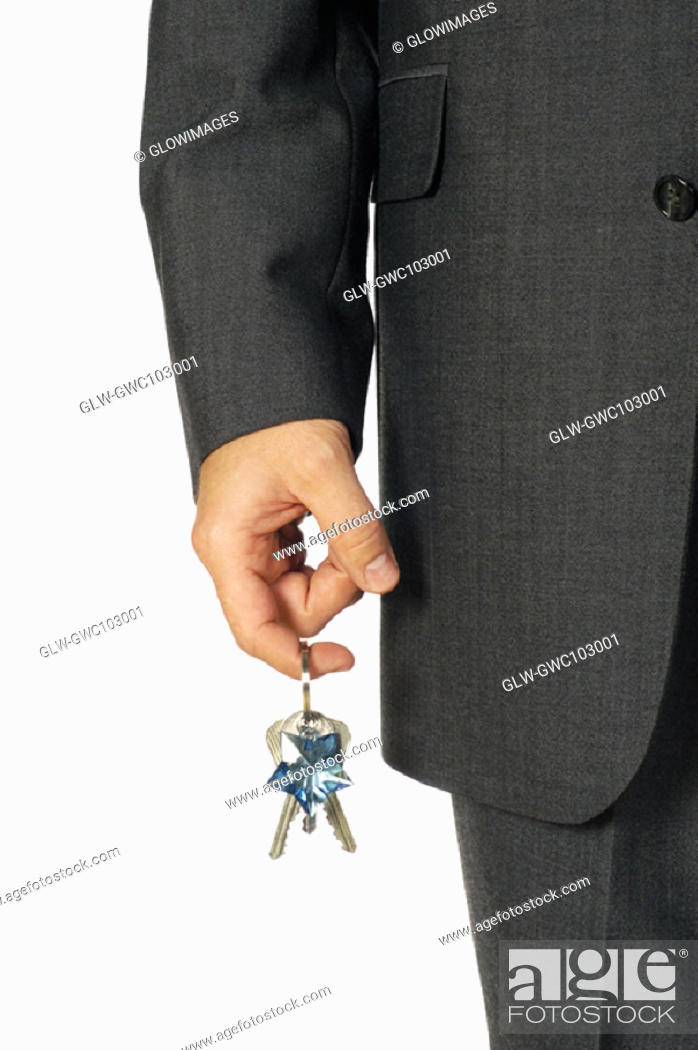 Stock Photo: Mid section view of a businessman holding keys.