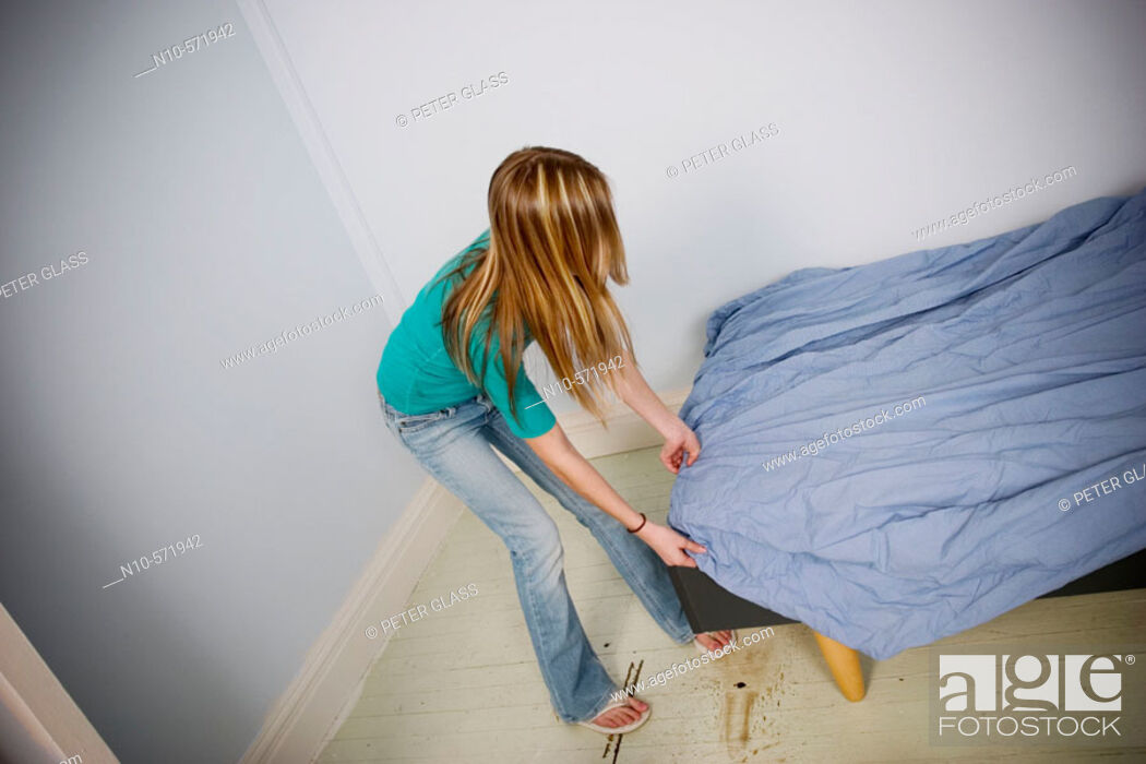 Stock Photo: Long blond-hair teen girl putting a sheet onto a bed.