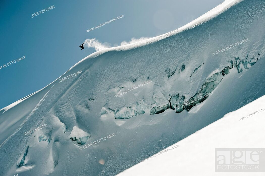 Imagen: A professional, freeriding snowboarder flips mid-air on a snowy slope against a blue sky; British Columbia, Canada.