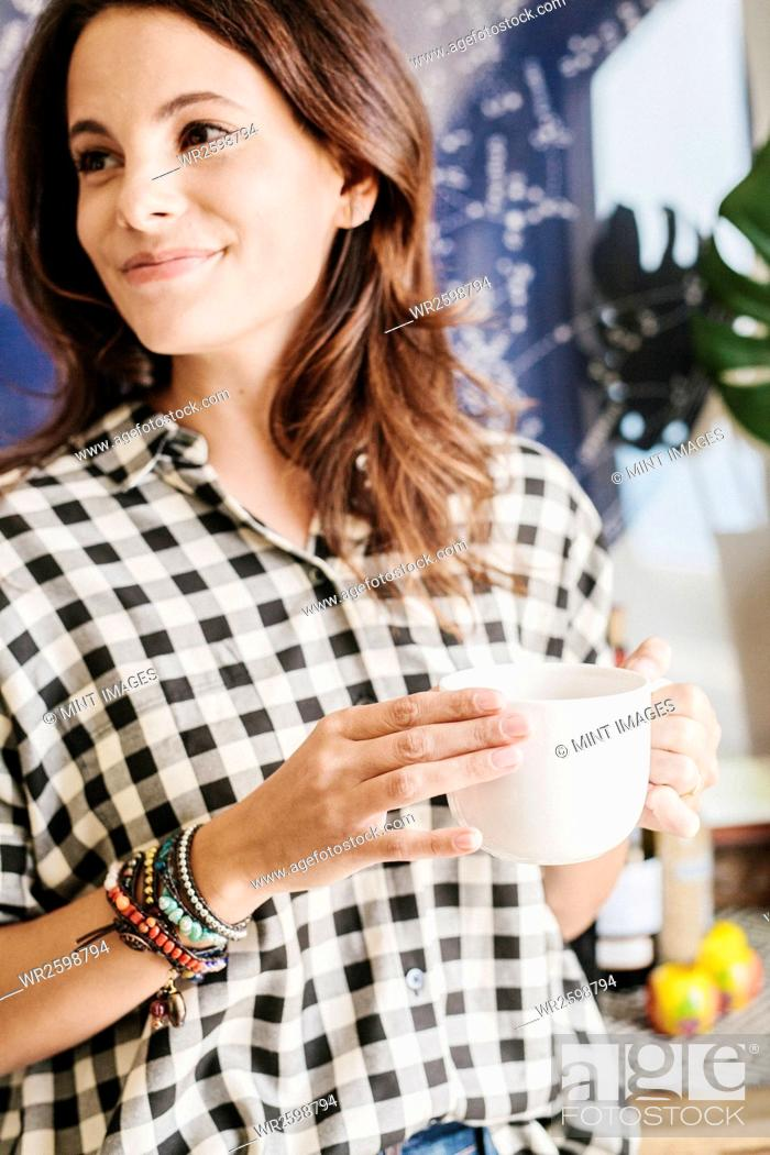 Stock Photo: Woman with long brown hair, wearing a chequered shirt, holding a mug.