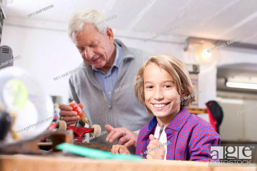 Stock Photo: Germany, Leipzig, Grandfather and son repairing skateboard.