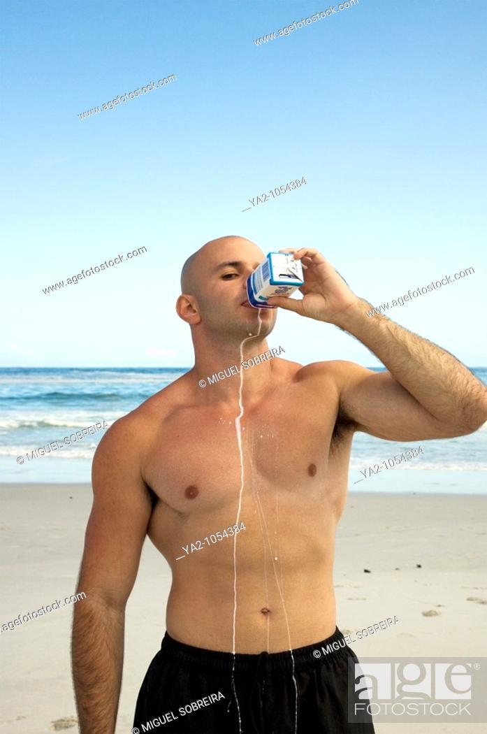 Stock Photo: Muscle man drinking milk from carton on the beach.