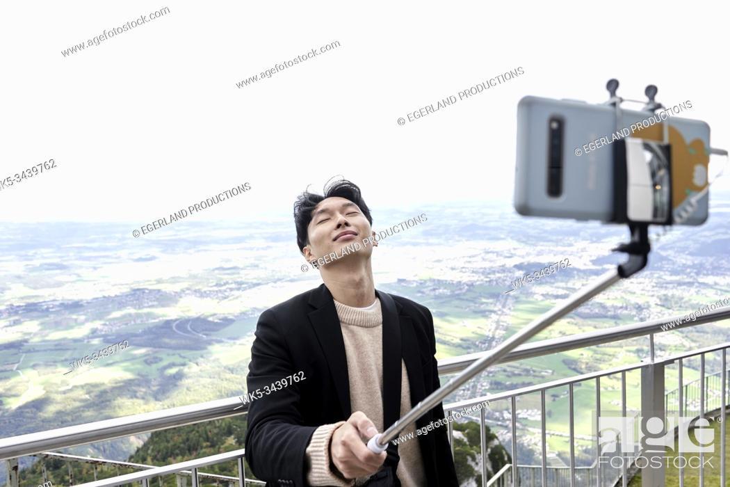 Stock Photo: Korean tourist man taking selfie at mount Untersberg with view at Salzburg, Austria, Europe.