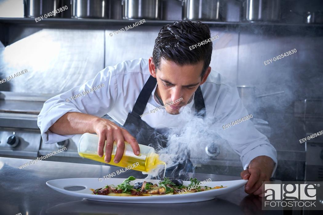 Stock Photo: Chef preparing octopus recipe in kitchen with smoke and oil.