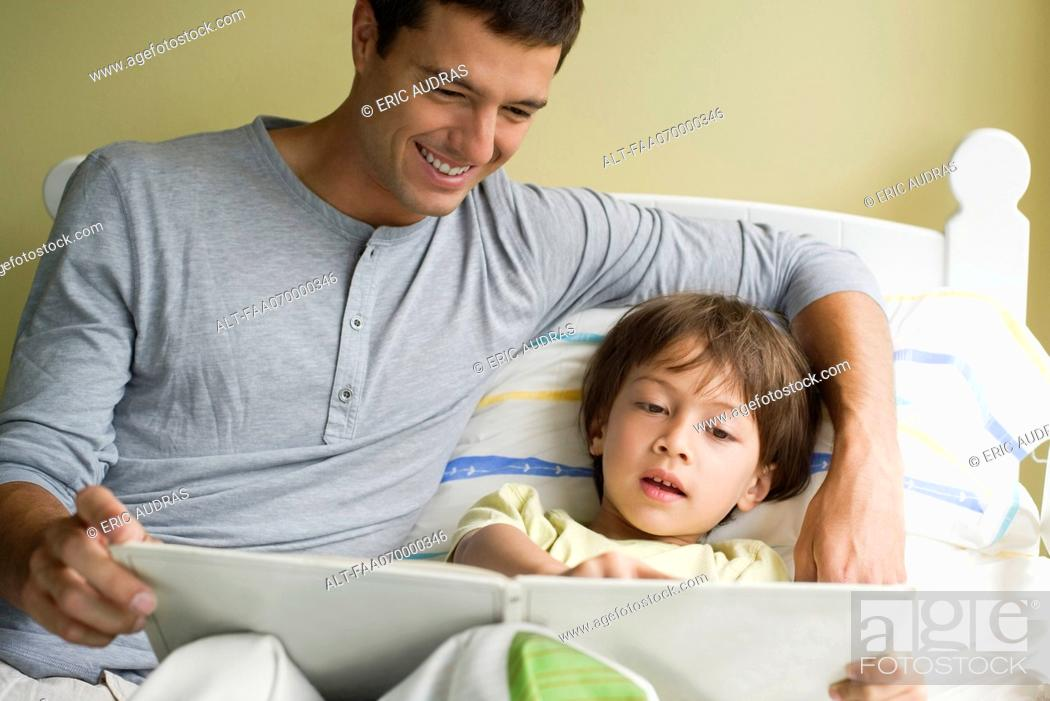 Stock Photo: Father and son reading story together.