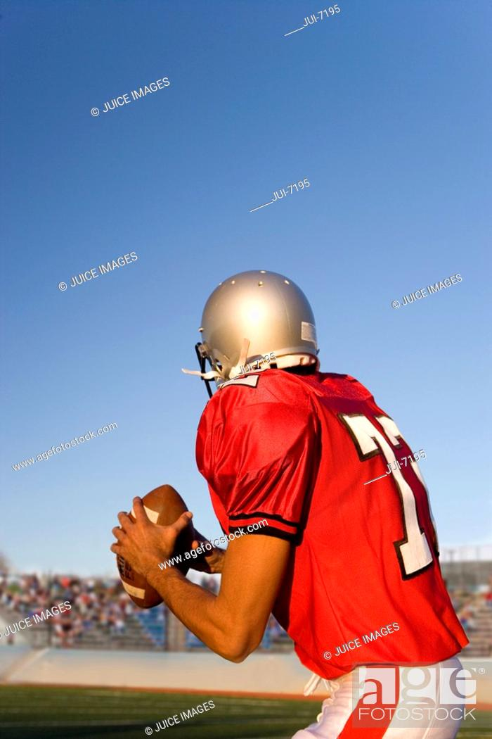 Stock Photo: American football quarterback, in red strip, looking to throw ball during competitive game, rear view.