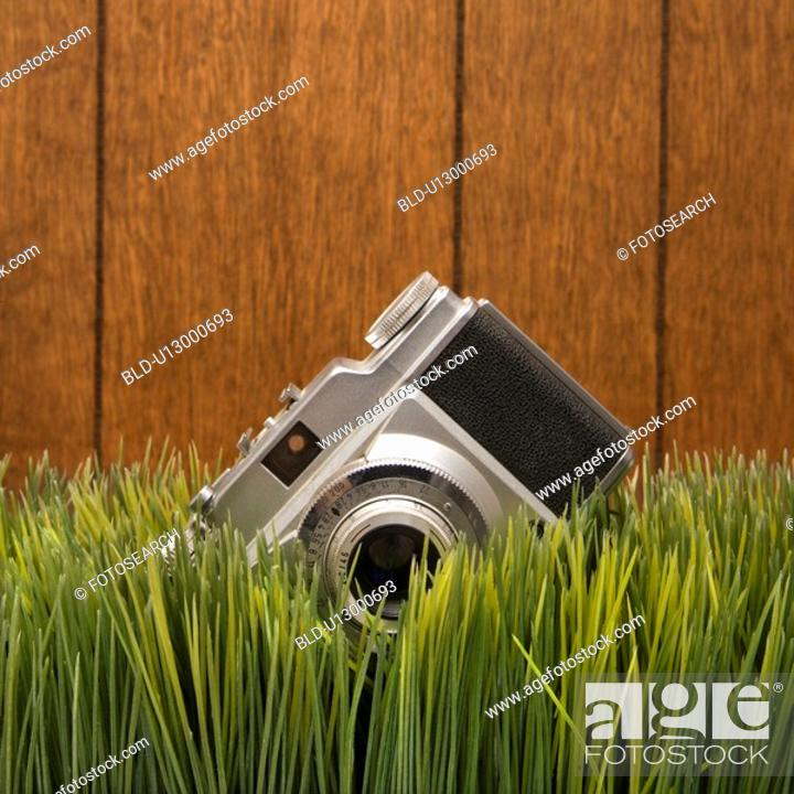 Stock Photo: Studio shot of vintage camera with wood paneling in background.