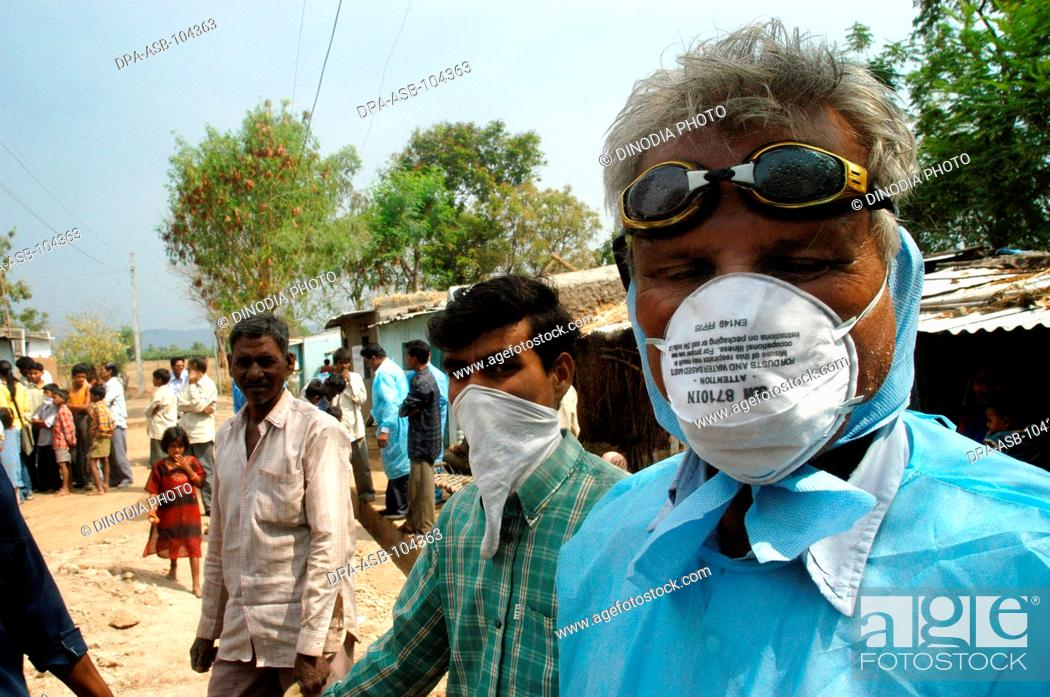 Stock Photo: Health workers cover their faces with protective masks as the go house to house to cull infected chickens in the backyard of the villager's houses at Hingona.
