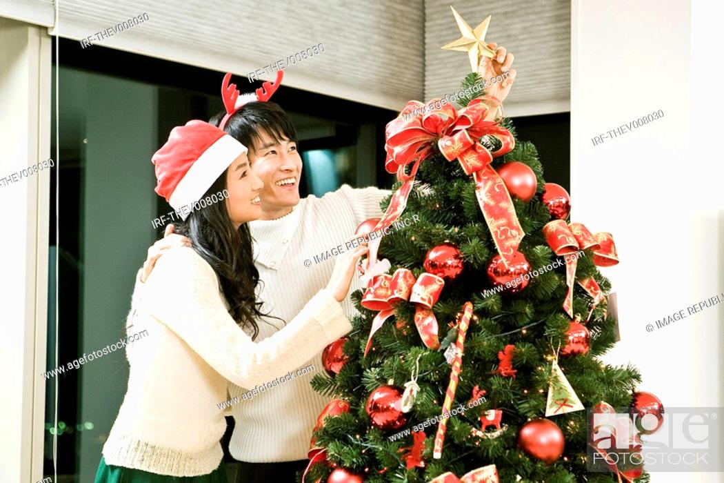 Stock Photo: young man and woman with the Christmas tree.