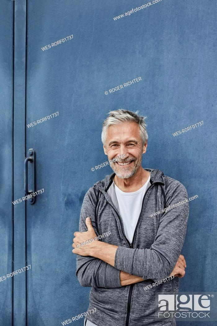 Stock Photo: Portrait of laughing mature man standing in front of gym.