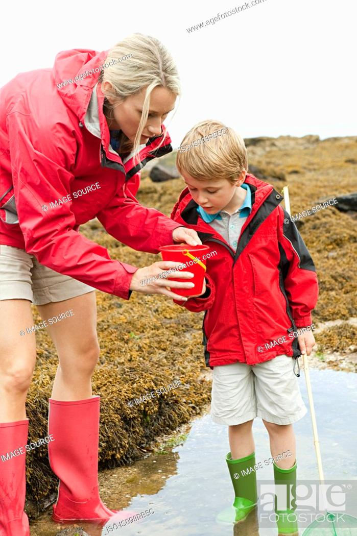 Stock Photo: Mother and son looking in rock pool.