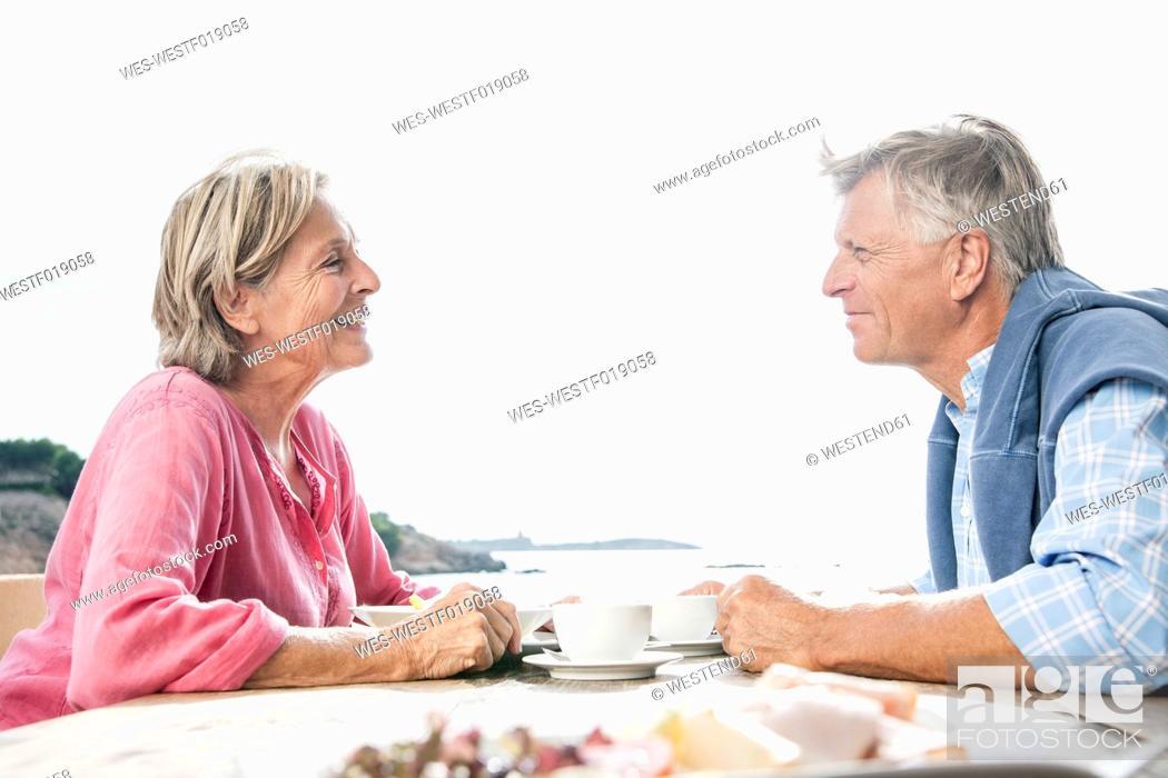 Stock Photo: Spain, Senior couple having lunch, smiling.