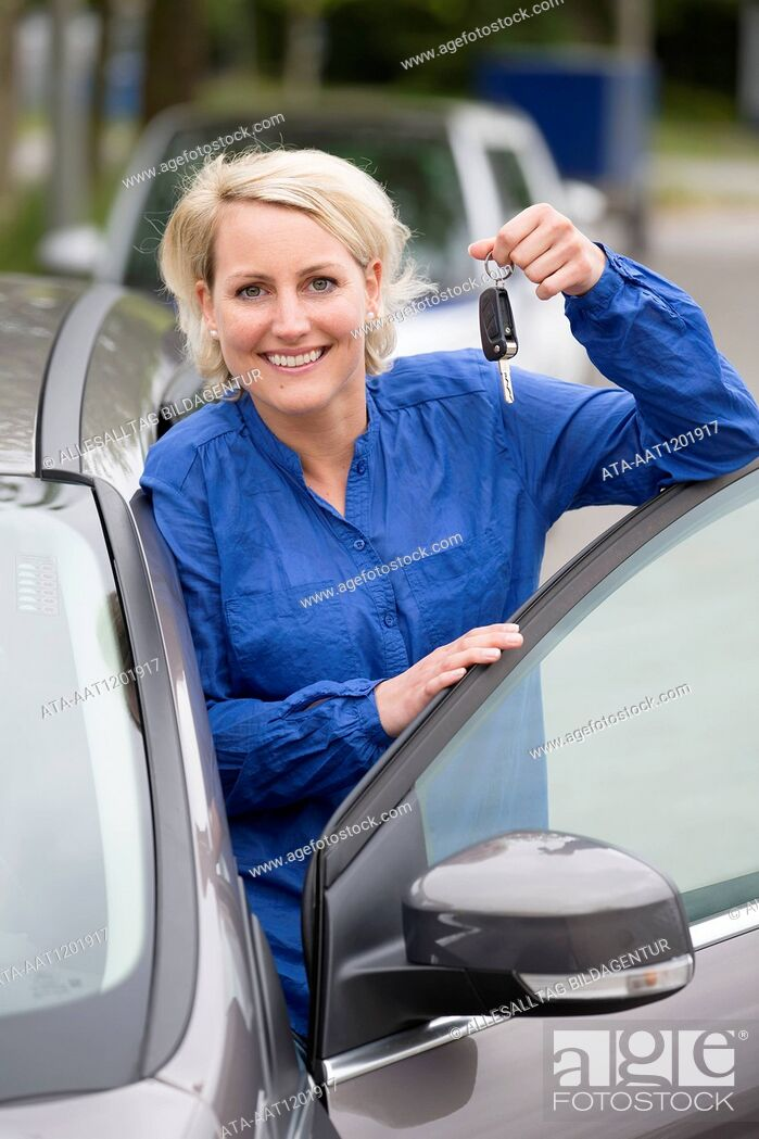 Stock Photo: Female car driver is holding a car key.
