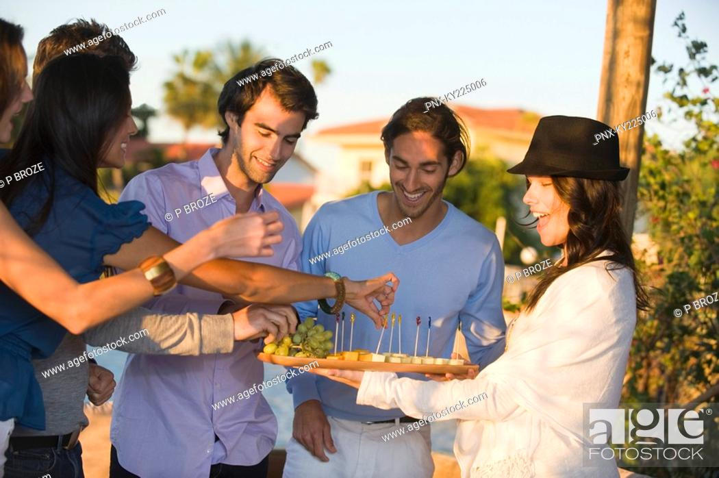Stock Photo: Woman serving fruits to her friends.