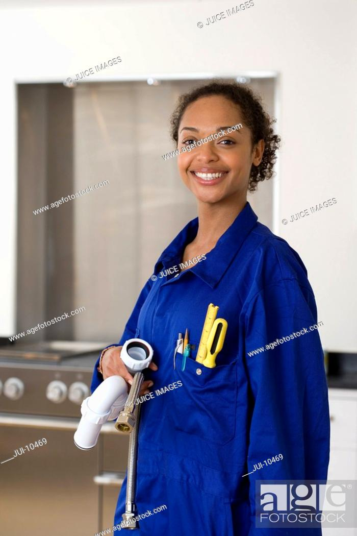 Stock Photo: Female plumber with pipes in kitchen, smiling, portrait.